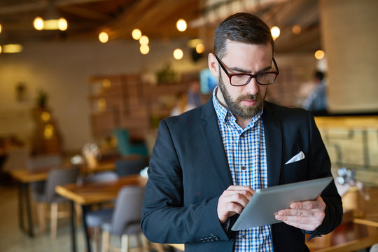 Waist-up portrait of concentrated bearded manager in eyeglasses checking business emails on digital tablet while standing at spacious modern restaurant