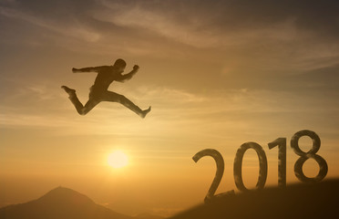 2018 brave man successful concept,silhouette man jumping over the sun between gap of the mountain to 2018 new year, feel like a winner, success, finish,reach a goal of live, jobs,work in year coming