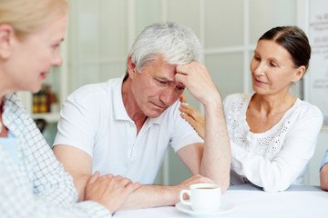 Two aged women comforting grey-haired man worried by his problems