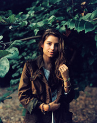 Portrait of a stylish woman in a coat standing by a tree