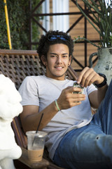Young Handsome Man Relaxing and Holding Mobile Phone