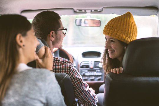 Three friends inside a car during a road trip.