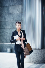 Smiling business woman walking out of the office building