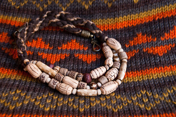 Tribal native bone beads from polymer clay fashion background on ornament fabric. Handmade jewelry.