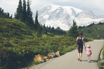 Mother and young daughter holding hands and walking on trail, Mt. Rainier in distance