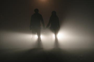Couple standing in the fog against car lights