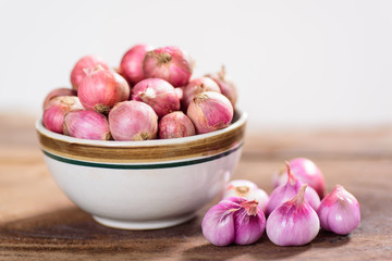 Fresh shallots in a bowl and wooden background, spice and herb, food ingredient
