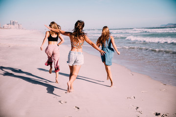 Group of girl friends running at the beach in summer