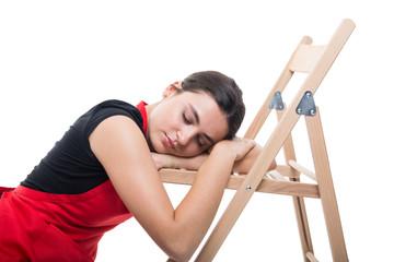 Tired female seller falling asleep on chair