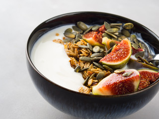 Healthy breakfast natural yogurt bowl with home made granola, pumpkin seeds and figs on gray background