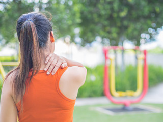 Young asian woman feel pain on her neck and shoulder while exercising, health care concept.