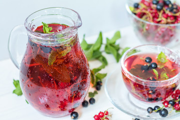 Fruit drink in transparent glass carafe and cup