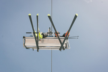 Skiers taking a chairlift in the alps.