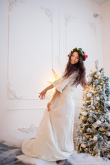 Beautiful girl in white dress and wreath on her head dancing on the bed
