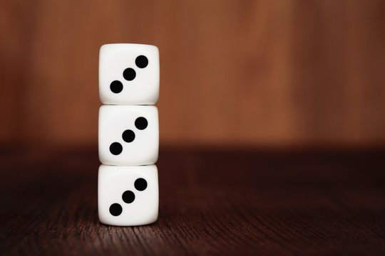 Three white plastic dices on each other on brown wooden board background. Six sides cube with black dots. Number 333.