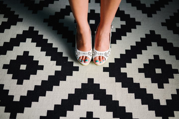 Girl in heels on geometiric pattern carpet