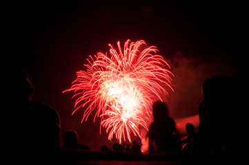 red fireworks with silhouettes of spectators  in foreground