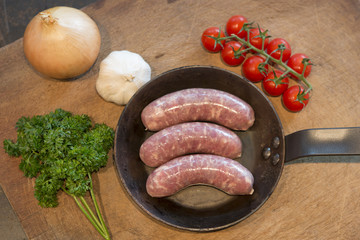 Uncooked sausages in a cast iron frying pan