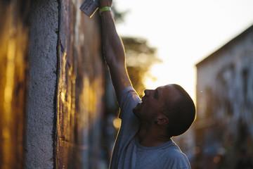 Street graffiti artist drawing on wall