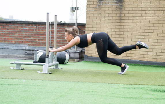 sled push woman pushing weights workout exercise