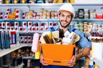 Workman holding basket with picked tools in paint store