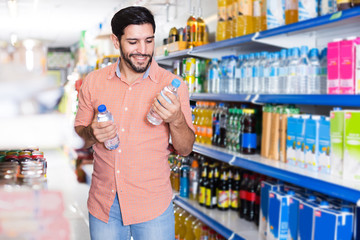 Portrait of man customer who is standing with drinks in supermarket.