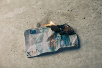 Burning twenty euro banknote.