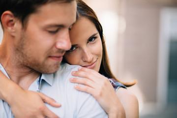 Young woman hugging boyfriend on street