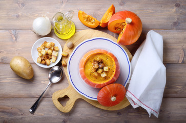Pumpkin soup with croutons in pumpkin bowl. Ingredients: Pumpkin, potatoes, white onion, extra virgin olive oil, nutmeg, salt and bread