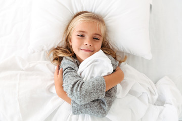 Top view portrait of a cute little girl hugging pillow