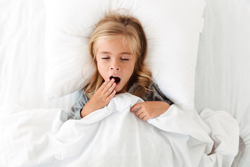 Top view of little girl yawns with closet eyes, covering her mouth while lying in bed