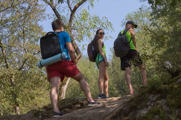 Eco tourism and healthy lifestyle concept. Three young Tourists With Backpacks travel