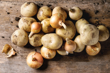Raw whole organic potatoes with soil, onion, garlic over old wooden background. Top view with copy space