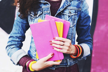 Young woman holding colorful copybooks in her hands with red nails
