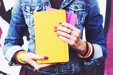 Girl in denim jacket with colorful copybooks