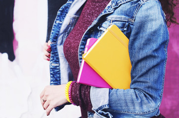 Girl in denim jacket with colorful diaries in her hands
