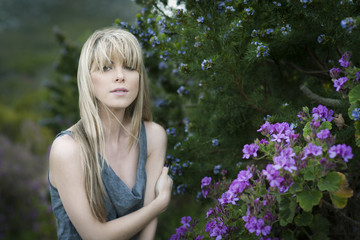 Young pretty blond girl in her 20's standing in amongst foliage and wild flowers