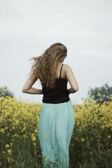 Back view of a young woman standing on the meadow