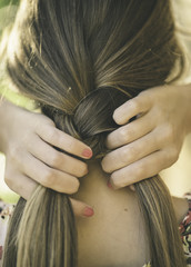 Young woman making a braid in her hair.