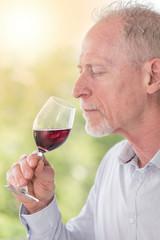 Mature man tasting red wine, light effect