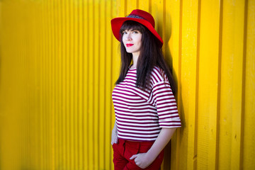 fashion concept - portrait of young woman in red posing over yellow wall