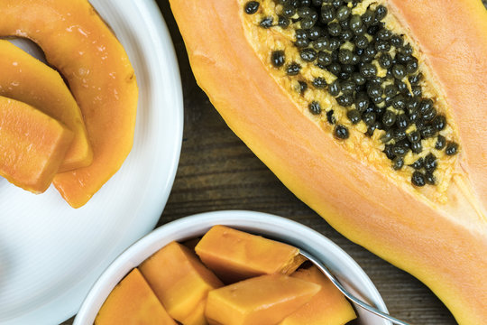 Close up view of papaya cut in half with black seeds next to small pieces in bowl against wooden background