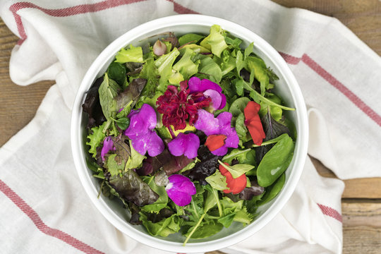 High angle view of mixed salad with eatable flowers in bowl standing on dishcloth