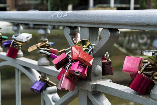 Colorful padlocks fixed at bridge balustrade as symbol of love