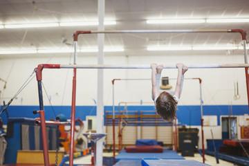 Cute preschool girl hanging on bars at gymnastics