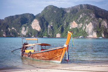 Beach with white sand landscape. Boat mooring in Asian style, canoe. Phi Phi Don. Thailand
