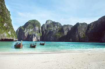 Beach with white sand landscape. Boat mooring in Asian style, canoe. Phi Phi Ley Thailand