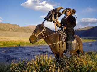 Mongolian man on a horse with an eagle