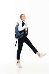 Full length image of pleased gigner student woman with backpack