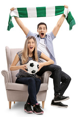 Excited football fans sitting in an armchair and cheering
